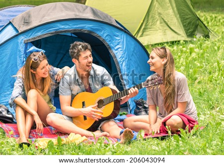 Group of best friends singing and having fun camping together - Concept of carefree youth and freedom outdoors in the nature - Caucasian young people during vacations - stock photo