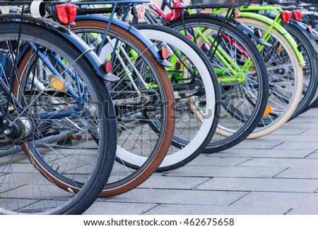 Group of bicycles in the row on sidewalk. Selective focus. Parking for bikes in big European city. Close up of wheel.