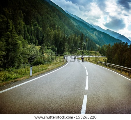 Group of bikers on mountainous road, fresh green forest, Alpine mountain, traveling on motorbike, active sport, speed concept - stock photo
