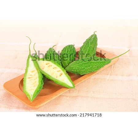 Group of bitter melon or bitter gourd on wooden dish. - stock photo