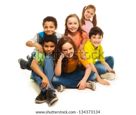 Group of black and Caucasian kids sitting happy together, smiling and laughing - stock photo