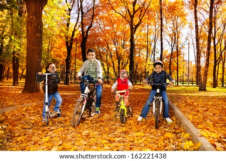 Group of black boys and girl, brothers and sister riding bicycles and scooter in the autumn October park with maple leaves - stock photo