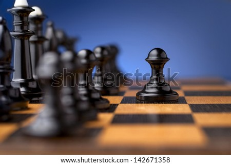 group of black chess on a chessboard and a black pawn in front of them - stock photo