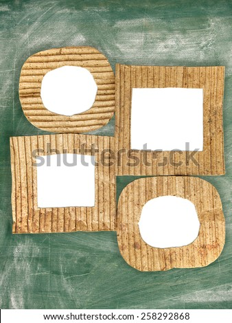 Group of blank cardboard frames on grunge chalkboard - stock photo
