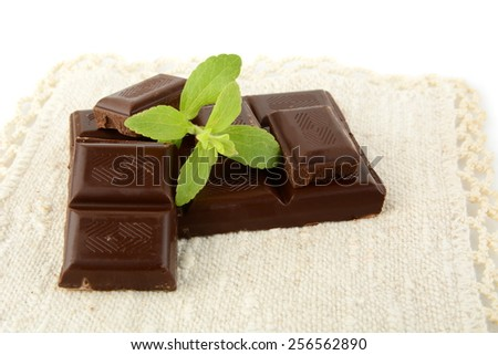 Group of blocks of chocolate with leaves of sage on white material like flax - stock photo