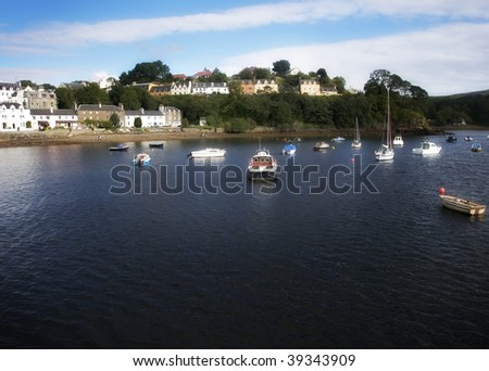 Group of boats anchored at Portree Harbour with row of colorful houses on Isle of Skye, Scotland - stock photo