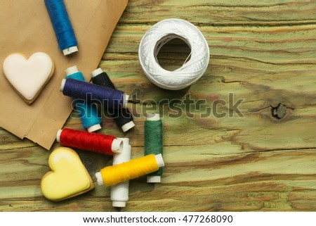 Group of bobbins of cotton colorful thread two homemade cookies in shape of heart and hank of yarn laying on pack paper and wooden background