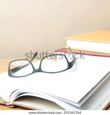 group of book and eyeglasses on wood background
