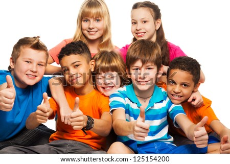 Group of boys and girls Caucasian and black showing thumb up - stock photo