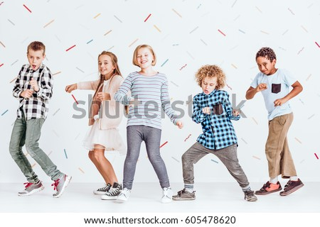 Group of boys and girls dancing at a party in a room