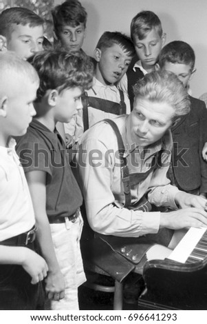 Group of boys having piano lesson with teacher