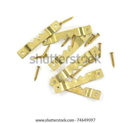 Group of brackets and nails to hang pictures on a white background.