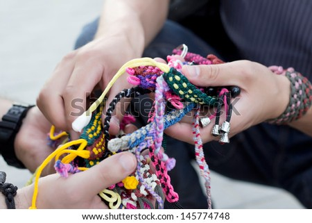 Group of bright and color bracelets in hands - stock photo