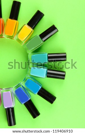 Group of bright nail polishes, on green background - stock photo