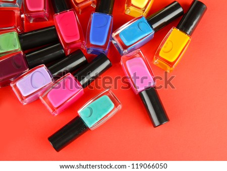 Group of bright nail polishes, on red background - stock photo