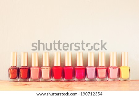 Group of bright nail polishes  over wooden board. retro filter. room for text - stock photo