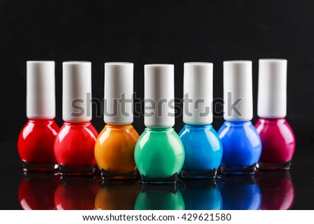 Group of bright nail polishes sorted like a rainbow. Bottles are standing in a row on black glossy surface with reflection. There is place for your logo on the lids of bottles. - stock photo
