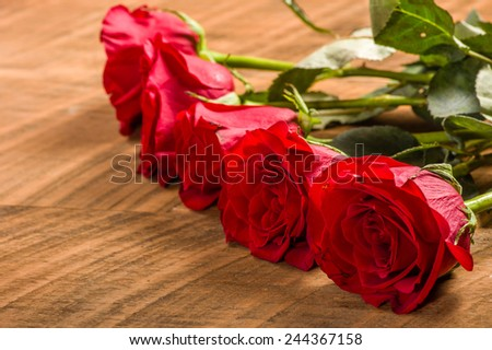 Group of bright red roses on a wooden table - stock photo