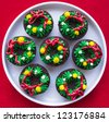 Group of brownies with wreath icing decoration on red tablecloth - stock photo