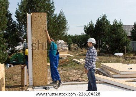 Group of builders erecting insulated wooden wall panels on the newly laid floor of a new build house on a residential plot - stock photo
