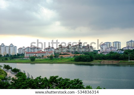 Group of buildings in the town behind the river underneath clouds sky