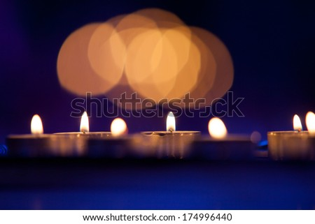 Group of burning candles at a blue background with selective focus