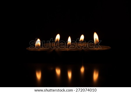 Group of burning candles on  black background. - stock photo