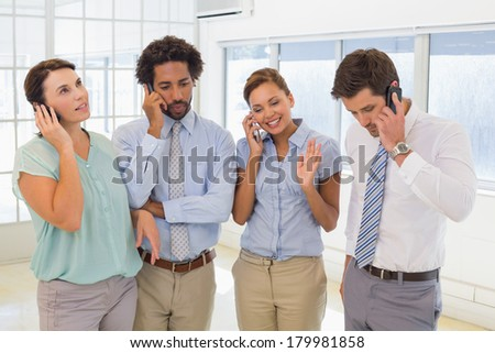 Group of business colleagues using mobile phone in the office - stock photo