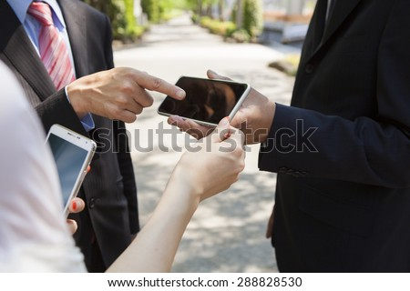 Group of business colleagues using mobile phone's outside