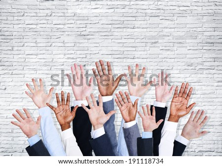 Group of business human arms raised with brick wall. - stock photo