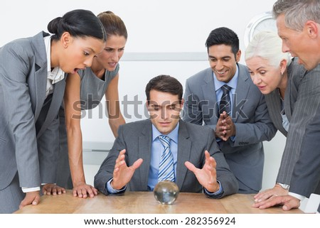 group of business man predict the future with a crystal ball - stock photo