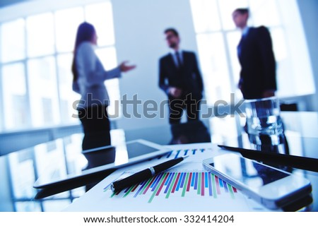 Group of business objects and gadgets on background of managers - stock photo