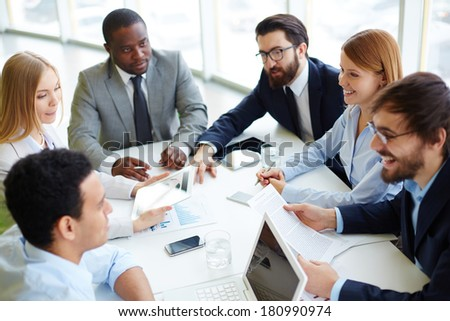 Group of business partners communicating at meeting in office - stock photo