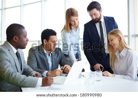 Group of business partners discussing ideas and planning work in office - stock photo
