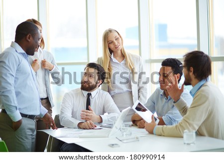 Group of business partners interacting in office - stock photo