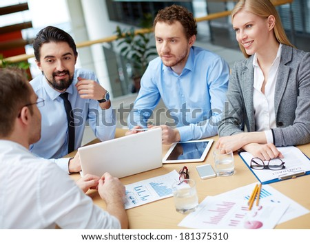Group of business partners interviewing young man at meeting - stock photo