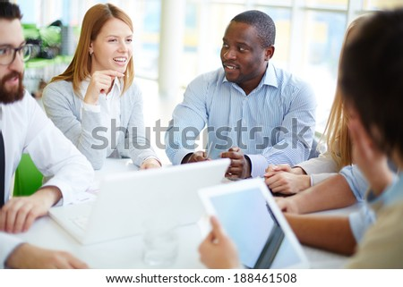 Group of business partners listening to one of colleagues at meeting - stock photo