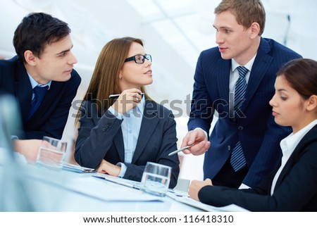 Group of business partners listening to young manager at meeting - stock photo