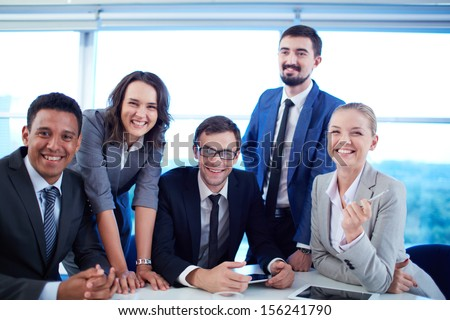 Group of business partners looking at camera with smiles in office - stock photo