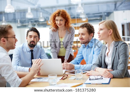 Group of business partners looking at young man presenting computer project at meeting - stock photo