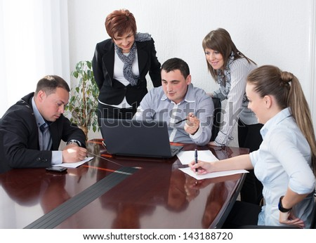 Group of business people analyzing and discussing during a working meeting in a modern office. - stock photo