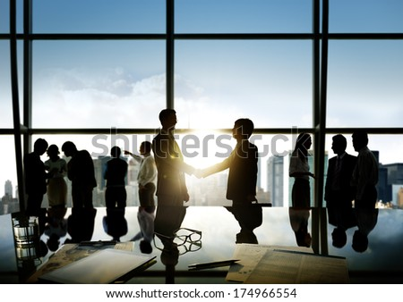 Group of business people and men handshake reflected onto table with documents. - stock photo