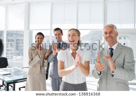 Group of business people applauding together in the meeting room - stock photo