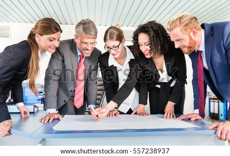 Group of business people are leaning over a desk and analyze graphs