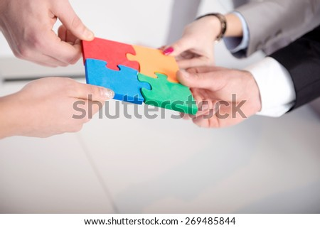 Group of business people assembled jigsaw puzzle and represent interpersonal cooperation and success - stock photo