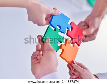 Group of business people assembling jigsaw puzzle and represent  - stock photo
