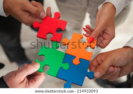 Group of business people assembling jigsaw puzzle and represent team support and help concept in office.