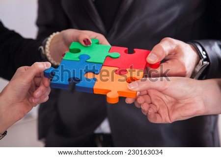 Group of business people assembling jigsaw puzzle and represent team support and help concept in office - stock photo