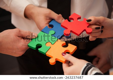 Group of business people assembling jigsaw puzzle and represent team support and help concept in office