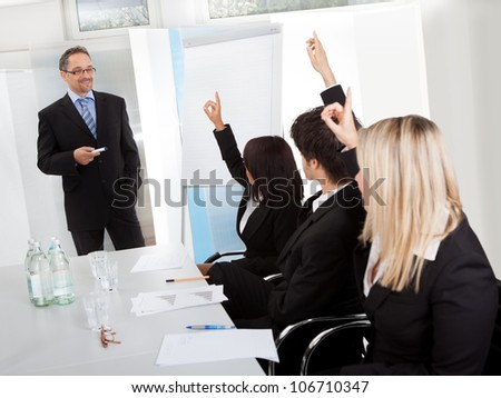 Group of business people at presentation raising hands in the office